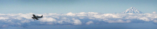 Airplane flying over clouds with a mountain snowy peak in the background