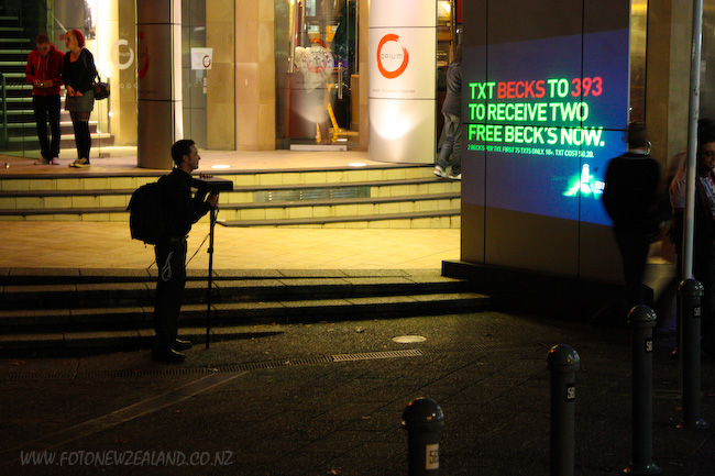 A guy with a projector in Queen St Auckland advertising Beck's beer.