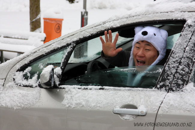 Funny asian driver in a bear hat in Lauterbrunnen Switzerland