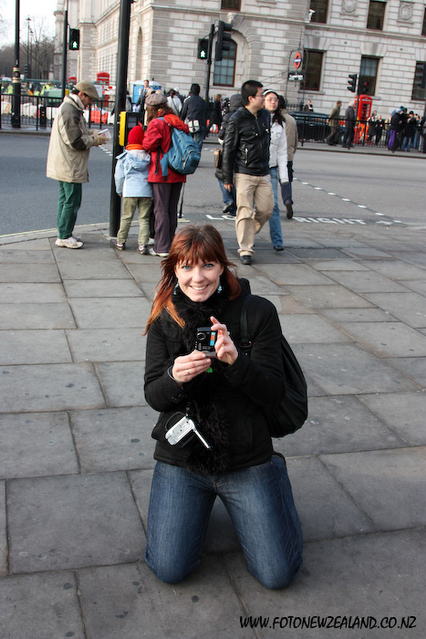 A girl with a camera smiling on her knees in London
