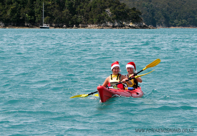 Girls wearing Santa Claus hats kayaking in Abel Tasman National Park, New Zealand